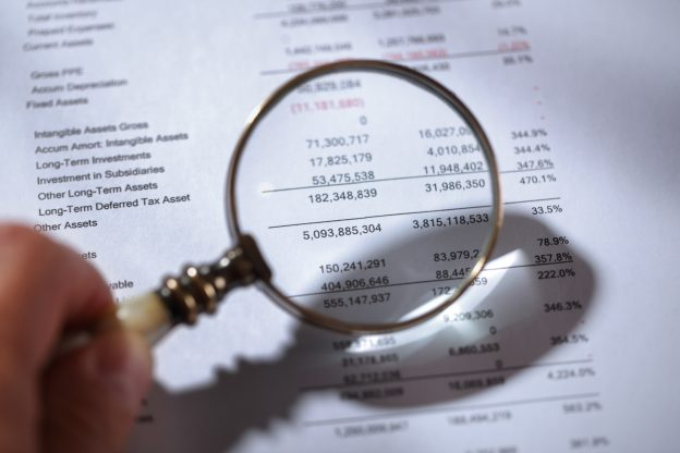 Magnifying glass examining financial statements