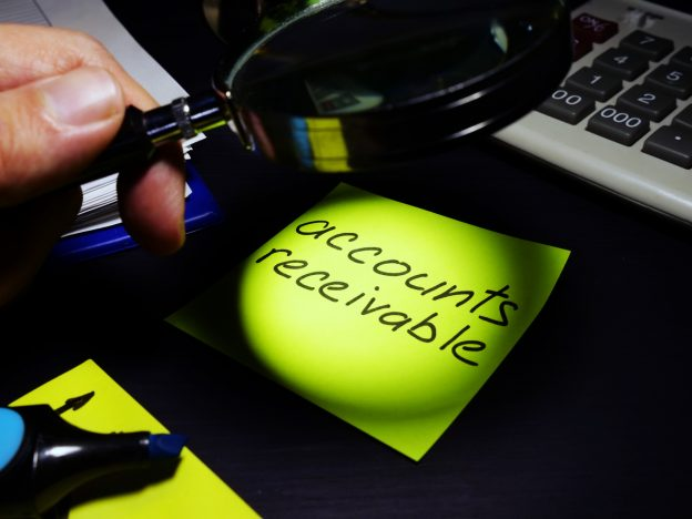 Magnifying glass examining sticky note with accounts receivable written on it.