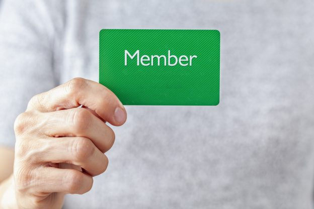 Hand holding up green member's card.
