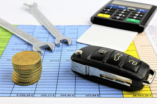 A concept image of car maintenance costs with keys, wrench, calculator and coins on financial spreadsheet