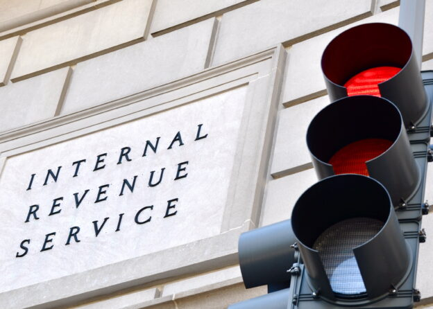 Red traffic light in front of Internal Revenue Service building