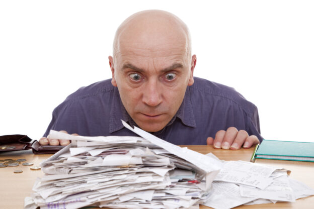 Man staring at pile of taxes trying to figure out how to make tax preparation more efficient