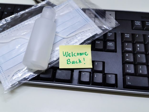 Key board with sticky on it saying 'welcome back' and face masks and hand sanitizer close by